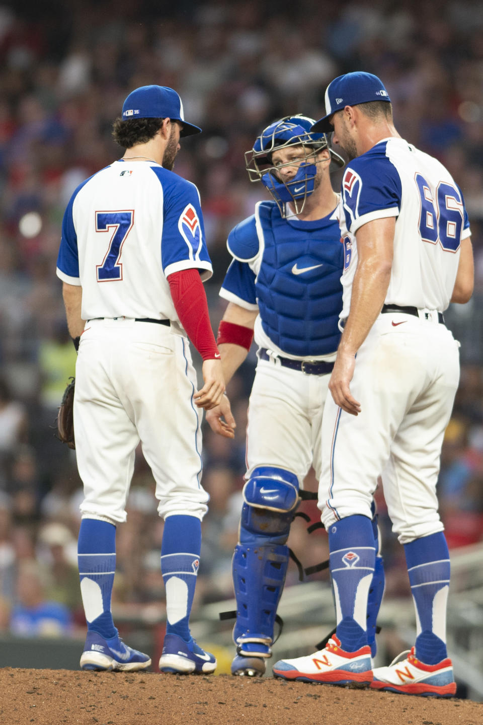 Atlanta Braves' Stephen Vogt, center, and Dansby Swanson, left, visit pitcher Kyle Muller (66) on mound during the fourth inning of a baseball game against the Milwaukee Brewers, Saturday, July 31, 2021, in Atlanta. (AP Photo/Hakim Wright Sr.)