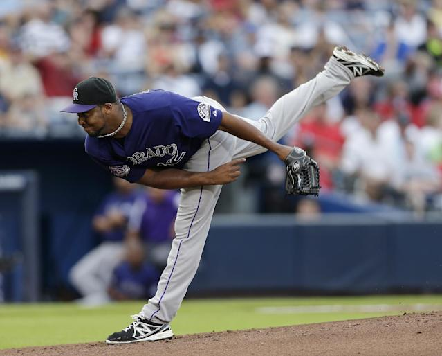 Colorado Rockies starting pitcher Juan Nicasio follows through in the first inning of a baseball game against the Atlanta Braves in Atlanta, Tuesday, July 30, 2013. (AP Photo/John Bazemore)