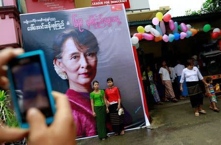 Supporters of Myanmar pro-democracy leader Aung San Suu Kyi pose in front of her picture as they celebrate her 69th birthday at the National League for Democracy party head office in Yangon