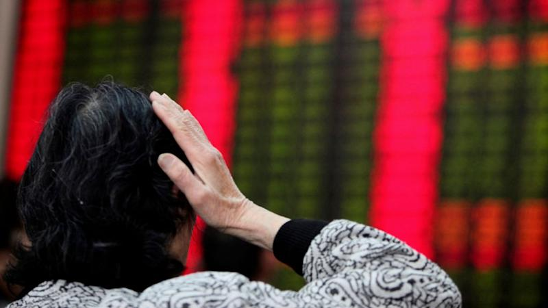 An investor looks at a stock price monitor