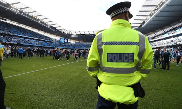 A policeman watches on after Manchester City's supporters came on to the Etihad Stadium pitch after the 5-0 win over Swansea, their first game since being confirmed as champions.