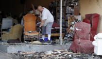 <p>Juan Moz, of Marshalltown, Iowa, helps clean out a tornado-damaged business on Main Street, Thursday, July 19, 2018, in Marshalltown, Iowa. Several buildings were damaged by a tornado in the main business district in town including the historic courthouse. (Photo: Charlie Neibergall/AP) </p>