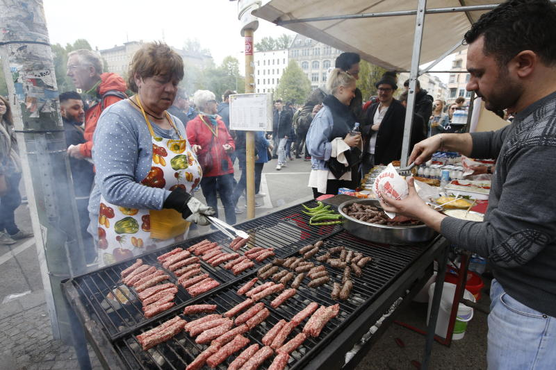 A woman grills sausages at the traditional MyFest street festival in Berlin's Kreuzberg district, Berlin , Germany, May 1, 2017. REUTERS/Fabrizio Bensch