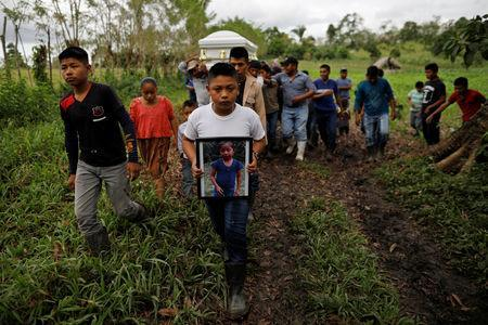 Friend and family carry a coffin with the remains of Jakelin Caal, a 7-year-old girl who handed herself in to U.S. border agents earlier this month and died after developing a high fever while in the custody of U.S. Customs and Border Protection, during her funeral at her home village of San Antonio Secortez, in Guatemala December 25, 2018. REUTERS/Carlos Barria