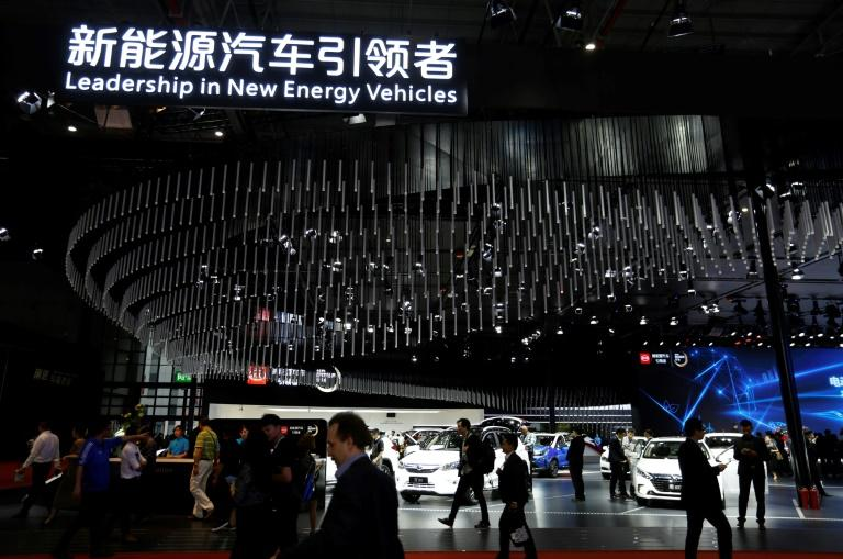 People visit the 'new-energy' vehicles area at the Shanghai Auto Show on April 19, 2017. With a quota threat looming, major manufacturers are announcing big plans to boost their electric vehicle (EV) offerings in China