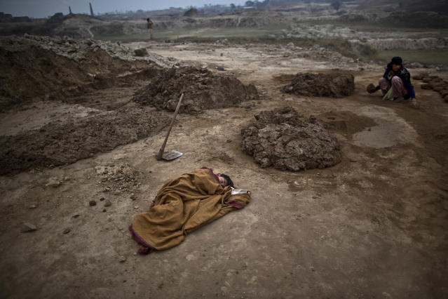 <p>Pakistani boy, Adil Shahid, 6, suffering from a fever, sleeps on the ground wrapped with a shawl, next to his mother Najma, 25, at the site of her work in a brick factory in Mandra, near Rawalpindi, Pakistan, March 3, 2014. (Photo: Muhammed Muheisen/AP) </p>