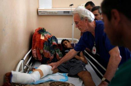 British vascular surgeon John Wolfe, who was invited to Gaza by the International Committee of the Red Cross (ICRC), checks a wounded Palestinian in a hospital in Gaza City April 24, 2018. REUTERS/Suhaib Salem