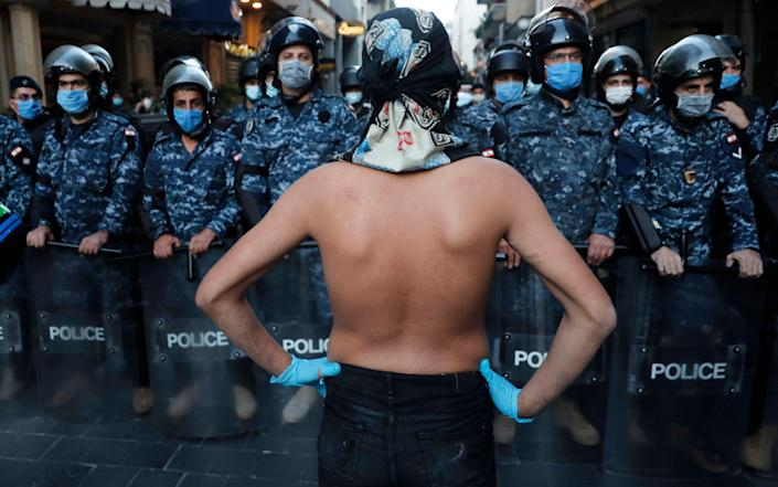An anti-government protester stands in front of the Lebanese riot police who wear masks to help curb the spread of the coronavirus, during a protest against the Lebanese central bank's governor Riad Salameh and against the deepening financial crisis