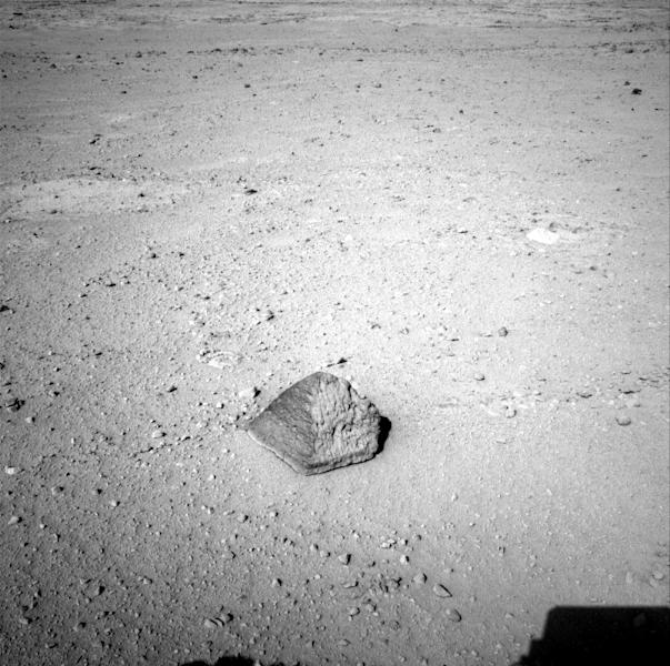 """This Wednesday, Sept. 19, 2012 photo provided by NASA shows a rock about 8 feet (2.5 meters) in front of the Curiosity rover on Mars. The rock is about 10 inches (25 centimeters) tall and 16 inches (40 centimeters) wide. The team has assessed it as a suitable target for the first use of Curiosity's contact instruments on a rock, and named it after the late Jacob Matijevic, who was the surface operations systems chief engineer for the Mars Science Laboratory Project and the project's Curiosity rover. (AP Photo/NASA/JPL-Caltech) The rock has been named """"Jake Matijevic."""" This commemorates Jacob Matijevic (1947-2012), who was the surface operations systems chief engineer for the Mars Science Laboratory Project and the project's Curiosity rover. He was also a leading engineer for all of the previous NASA Mars rovers: Sojourner, Spirit and Opportunity. Curiosity's contact instruments are on a turret at the end of the rover's arm. They are the Alpha Particle X-Ray Spectrometer for reading a target's elemental composition and the Mars Hand Lens Imager for close-up imaging."""