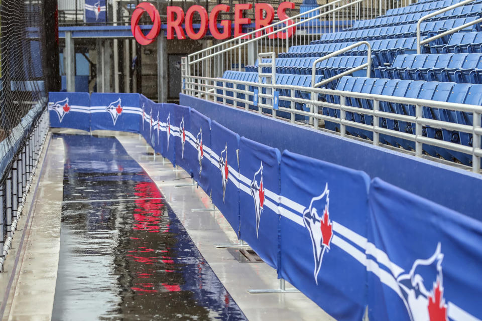 Rain delays the start of the baseball game between the Los Angeles Angels and Toronto Blue Jays on Sunday, April 11, 2021, in Dunedin, Fla. (AP Photo/Mike Carlson)