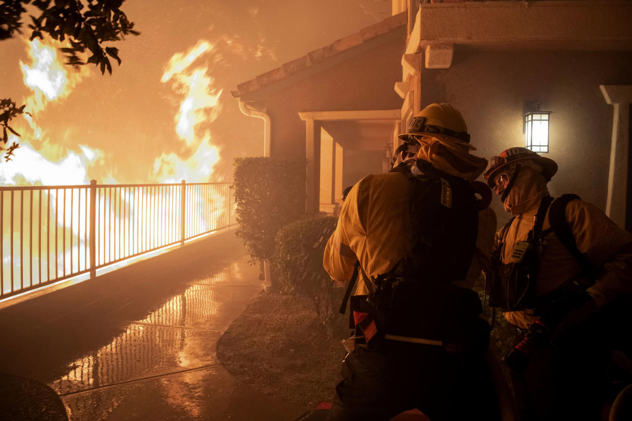 In this Thursday, Oct. 10, 2019 photo, firefighters work on a hose nozzle as the Saddleridge fire burns nears homes in Sylmar, Calif. (Photo: Michael Owen Baker/AP)