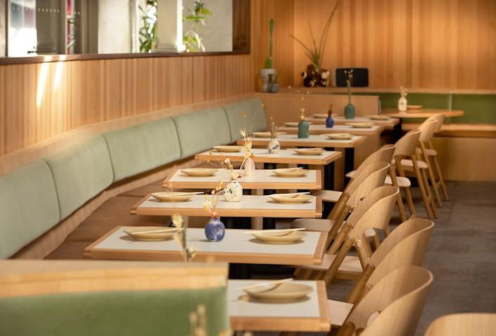 """<div class=""""caption""""> Jade velvet banquettes complement the heavy dose of wood in the seating area. </div>"""