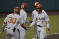 Texas' Douglas Hodo (7) celebrates with teammates after he scored against South Florida during the third inning of an NCAA Super Regional college baseball game, Sunday, June 13, 2021, in Austin, Texas. (AP Photo/Eric Gay)