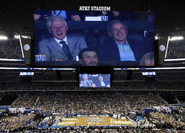 Former presidents Bill Clinton, left, and George W. Bush watch action between Connecticut and Kentucky during the first half of the NCAA Final Four tournament college basketball championship game Monday, April 7, 2014, in Arlington, Texas. (AP Photo/Tony Gutierrez)