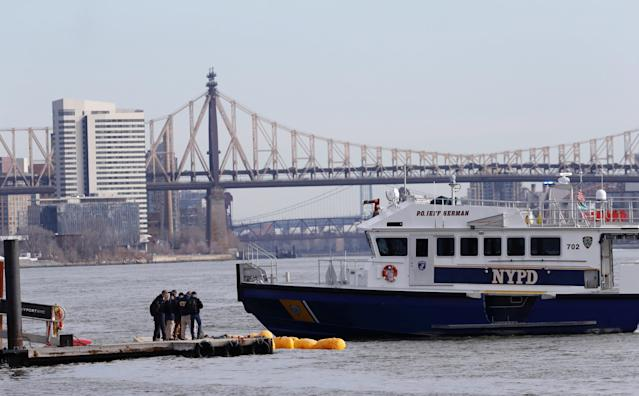 <p>Personnel with the NTSB look at the scene of a submerged helicopter in New York's East River, March 12, 2018. The pilot was able to escape the Sunday night crash after the aircraft flipped upside down in the water killing several passengers, officials said. (Photo: Mark Lennihan/AP) </p>