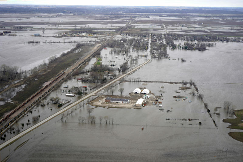 FILE- In this April 12, 2019 file photo, the flooded town of Pacific Junction, Iowa, is seen from above. Nebraska, Iowa, Kansas and Missouri are joining forces for a study that will look for ways the states can limit flooding along the Missouri River and give them information about how wetter weather patterns could require changes to the federal government's management of the basin's reservoirs. The states are pooling their money to pay for half of a $400,000 study with the U.S. Army Corps of Engineers to measure how much water flows down the Missouri River.  (AP Photo/Nati Harnik)