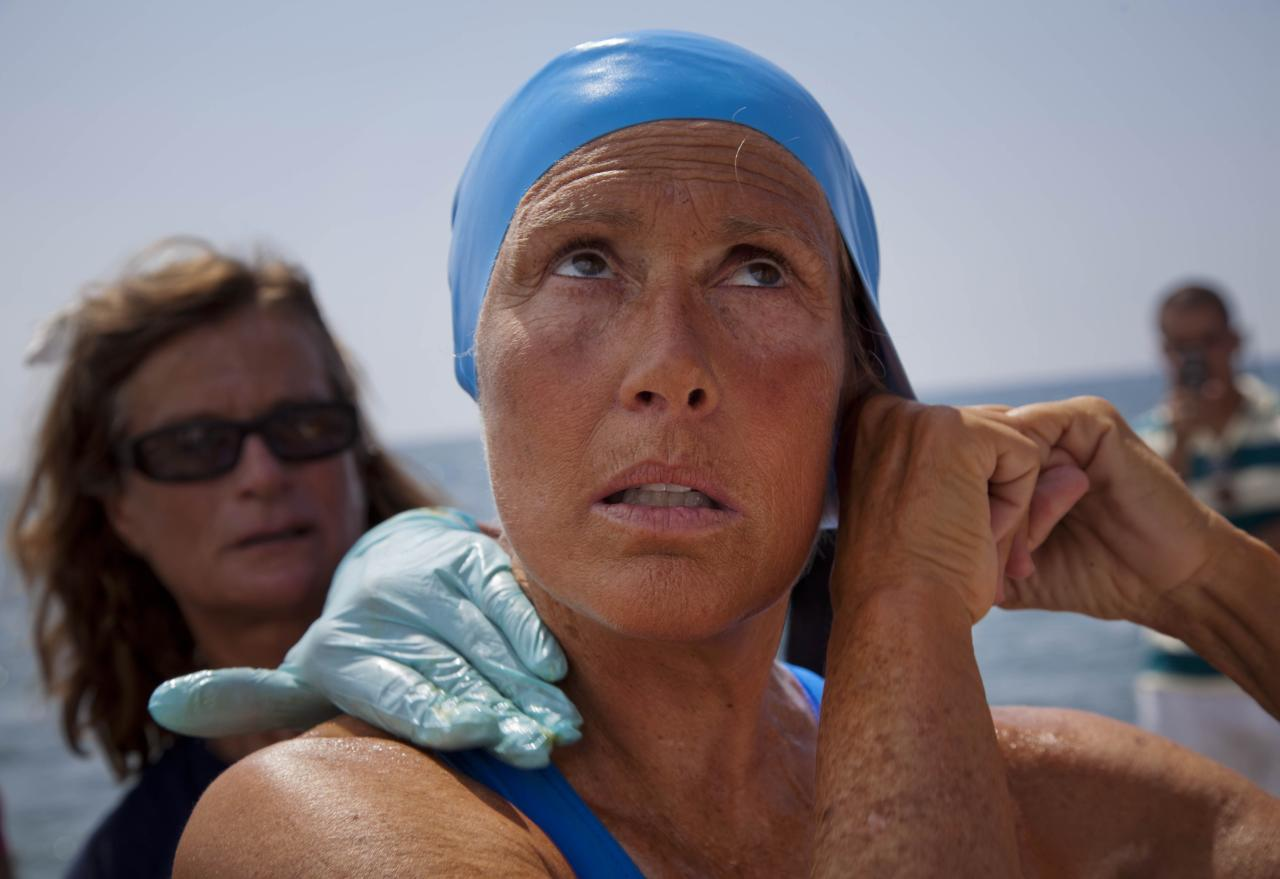 U.S. swimmer Diana Nyad adjusts her swimming cap as a woman applies a protective ointment to her skin as she prepares to jump into the water and start her swim to Florida from Havana, Cuba, Saturday, Aug. 18, 2012. Endurance athlete Nyad launched another bid Saturday to set an open-water record by swimming from Havana to the Florida Keys without a protective shark cage. (AP Photo/Ramon Espinosa)