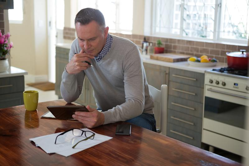 Older man in kitchen looking at tablet