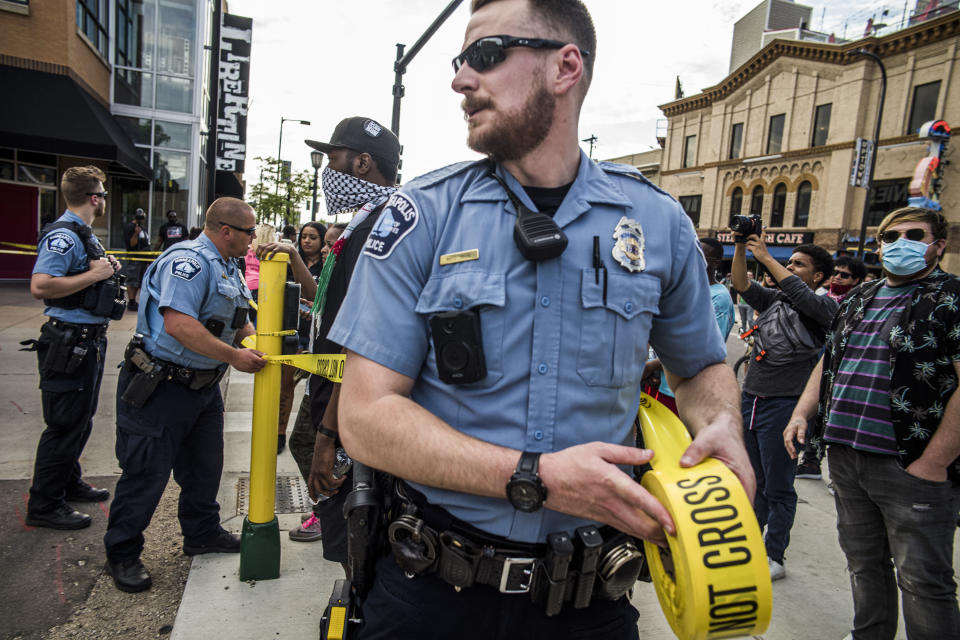 Police investigate a shooting as protesters gather on Thursday, June 3, 2021 in Minneapolis. Crowds vandalized buildings and stole from businesses in Minneapolis' Uptown neighborhood after officials said a man wanted for illegally possessing a gun was fatally shot by authorities. (Richard.Tsong-Taatari/Star Tribune via AP)