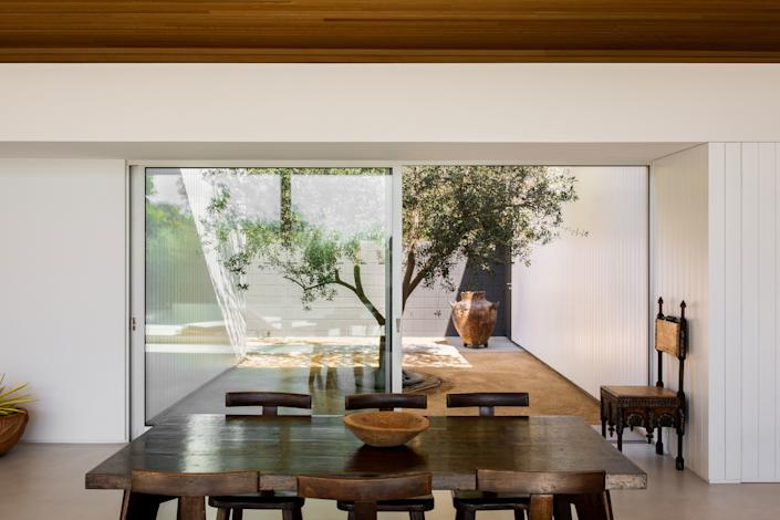 The home was designed so that the interior flows seamlessly into the exterior. Nowhere is this more apparent than the dining room, where a large sliding door looks out onto a picturesque olive tree. The table is a 1930s Pierre Jeanneret, the chairs are 1950s Olavi Hanninen, and the chair against the wall is by Carlo Bugatti and dates to 1906.