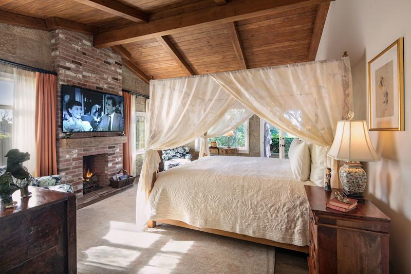 Inside a cottage guest room with a four-poster canopy bed.