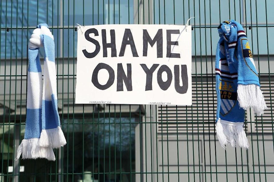 <p>Fans respond to announcement of a European Super League with Manchester City scarves outside the Etihad Stadium on 20 April</p> (Getty Images)