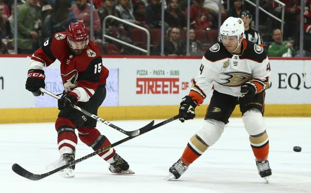 Arizona Coyotes center Brad Richardson (15) passes the puck around Anaheim Ducks defenseman Cam Fowler (4) during the first period of an NHL hockey game Tuesday, March 5, 2019, in Glendale, Ariz. (AP Photo/Ross D. Franklin)
