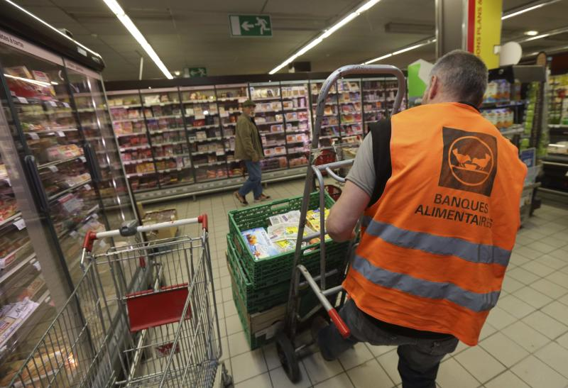 "Guy, a retired train driver, who volunteers at the ""Banques Alimentaires"", pushes a trolley with goods given by a supermarket to charity organisations in l'Hay-les-Roses"