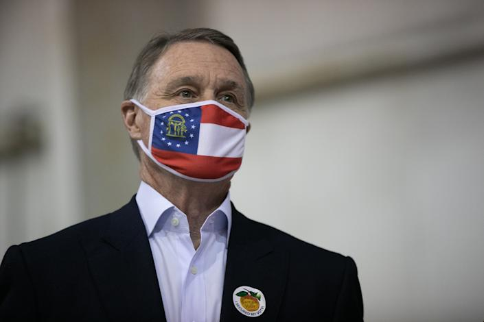 Sen. David Perdue wears a face mask emblazoned with the Georgia state flag