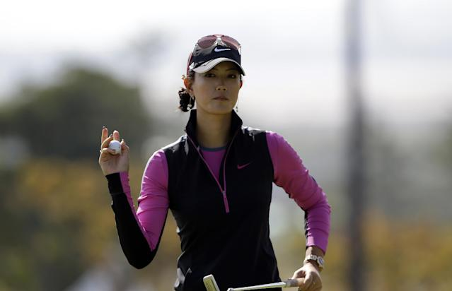 Michelle Wie of the United States acknowledges cheers from the gallery after her putt on the third hole during the first round of the LPGA KEB Hana Bank Championship golf tournament at Sky72 Golf Club in Incheon, west of Seoul, South Korea, Friday, Oct. 18, 2013. (AP Photo/Lee Jin-man)