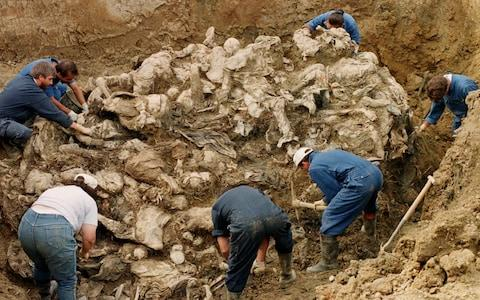 International War Crimes Tribunal investigators clearing away soil and debris from dozens of Srebrenica victims buried in a mass grave near the village of Pilica - Credit: Staton Winter / AP