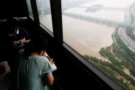 Visitors use their mobile phones as a flooded Han River park is seen in the background at an observatory platform in Seoul