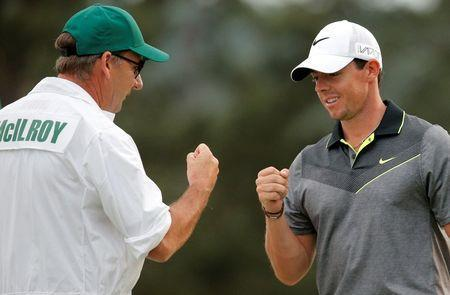 FILE PHOTO - Rory McIlroy of Northern Ireland bumps fists with his caddie J.P. Fitzgerald after making a birdie on the 18th hole during second round play of the Masters golf tournament at the Augusta National Golf Course in Augusta, Georgia April 10, 2015. REUTERS/Brian Snyder/File Photo