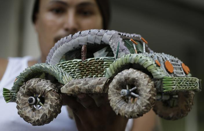 Venezuelan migrant Edixon Infante shows a handicraft made in with devalued Venezuelan currency, in Cucuta, Colombia, Wednesday, Feb. 6, 2019. The Venezuelan military blocked a border bridge where humanitarian aid is expected to arrive with a tanker and two cargo trailers, Colombian officials said Monday, in an apparent bid to stop the loads of food and other supplies from entering the country. (AP Photo/Fernando Vergara)