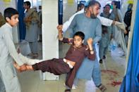 Volunteers carry a wounded boy into a hospital following the suicide attack on the funeral of a local police commander in Nangarhar on May 12, 2020 (AFP Photo/NOORULLAH SHIRZADA)