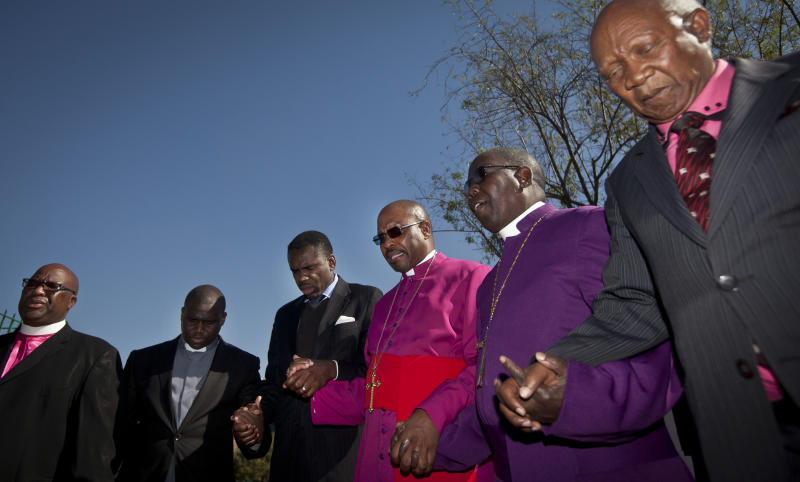 Bishop Abraham Sibiya, 3rd right, and other representatives of churches pray for the health of former South African President Nelson Mandela at the Mediclinic Heart Hospital where he is being treated in Pretoria, South Africa Friday, June 14, 2013. Nelson Mandela's health is improving but the 94-year-old beloved anti-apartheid hero remains in serious condition, South Africa's president said Thursday. (AP Photo/Ben Curtis)