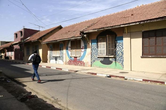 Painting the walls of old colonial buildings is meant to save them as developers move in (AFP Photo/SEYLLOU)
