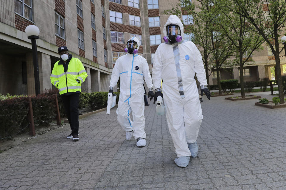Safety Director Tony Barzelatto, right, Environmental Specialist Anthony Olivieri, center, and Riverbay Corporation General Manager Noel Ellison leave a just disinfected building in Co-op City in the Bronx borough of New York, Wednesday, May 13, 2020. Regular cleanings occur throughout the common areas of the buildings while the heavy disinfecting occurs in response to specific incidents, in this case reports of two coronavirus cases on the same floor. Within the Bronx, almost no place has been hit as hard as Co-op City. (AP Photo/Seth Wenig)