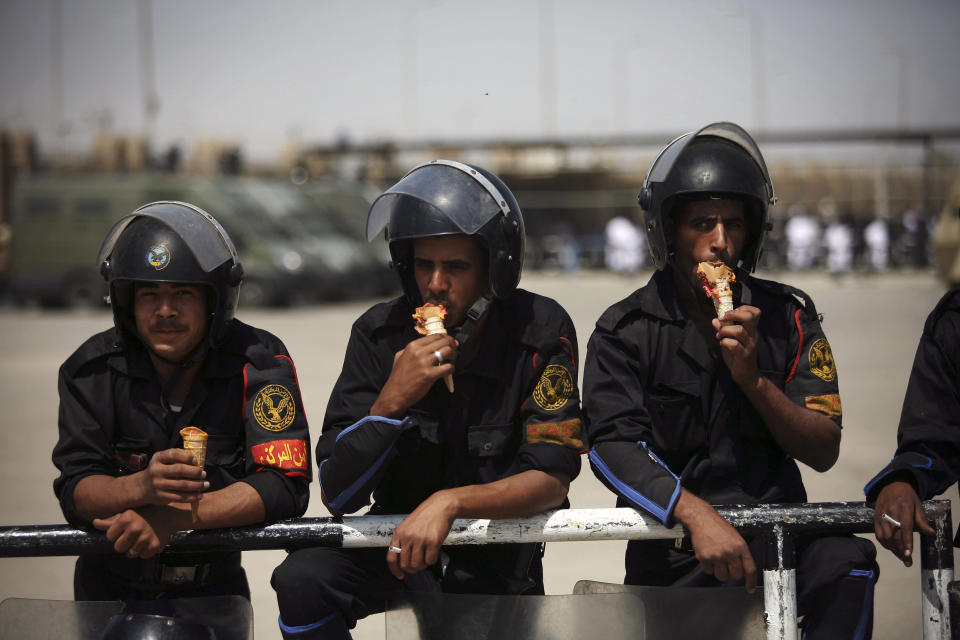 FILE - In this May 2, 2012 file photo, Egyptian riot police eat ice cream while securing the courthouse where ex-President Hosni Mubarak received a verdict in his trial for charges related to the death of protesters in Cairo, Egypt. The 2011 uprising led to the quick ouster of autocrat Hosni Mubarak. A decade later, thousands are estimated to have fled abroad to escape a state, headed by President Abdel Fattah el-Sissi, that is even more oppressive. (AP Photo/Manu Brabo, File)