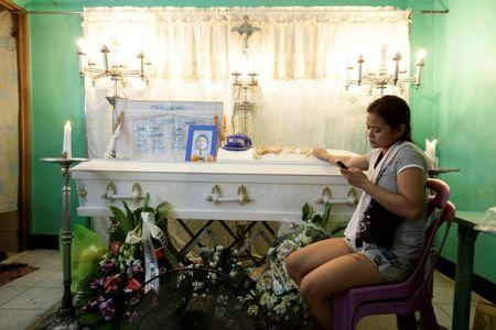 Jennelyn Olaires, 26, uses her mobile phone as she sits beside the coffin of her partner Michael Siaron in Pasay, Metro Manila, Philippines July 28, 2016. REUTERS/Czar Dancel