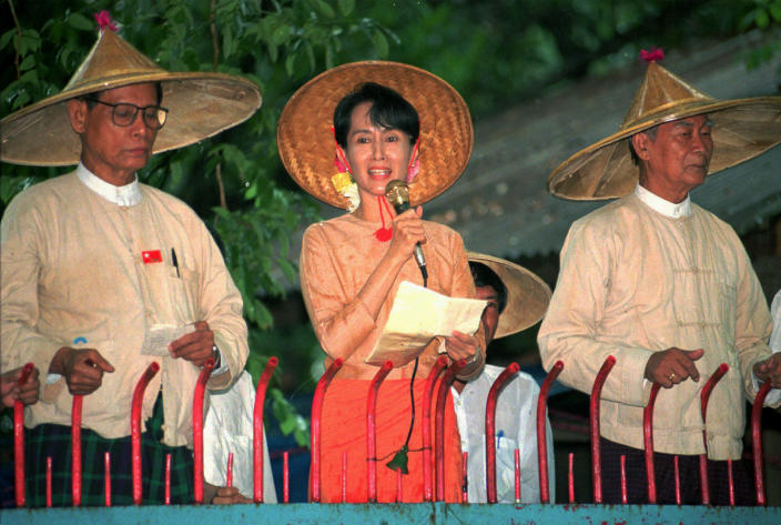 FILE - In this June 16, 1996, file photo, pro-democracy leader Aung San Suu Kyi, center, under house arrest speaks to supporters outside her home as senior leaders in the National League for Democracy Tin Oo, left, and U Kyi Maung listen, in Yangon, Myanmar. Suu Kyi was ousted in the Feb. 1, 2021 coup. As arrests of dissidents continue during anti-coup protests across Myanmar, experts are concerned that a new generation of political prisoners will begin to fill the country's prisons. (AP Photo/Stuart Isett, File)