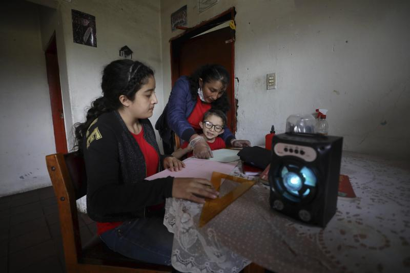 Fanny Mendez, right, mother of 14-year-old Marlene Beltran, left, and Felipe Beltrán, 5, helps her children at home to make a cube out of paper as they listen to an hour-long lesson broadcast by the Bacata Stereo radio station during the lockdown to prevent the spread of the new coronavirus in Funza, Colombia, Wednesday, May 13, 2020. The Beltrans work on dairy farms and have no internet connection at home, so the hour-long radio lesson developed by the municipal government keeps the children busy while schools are closed. (AP Photo/Fernando Vergara)