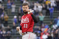 Cincinnati Reds' Jesse Winker gestures over to Chicago Cubs third base coach Willie Harris in the dugout during the fourth inning of a baseball game Friday, May 28, 2021, in Chicago. (AP Photo/Charles Rex Arbogast)