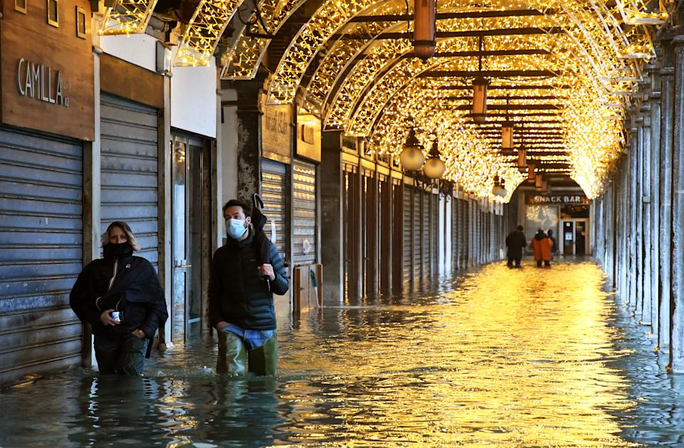"TOPSHOT - People walk across an arcade by a flooded St. Mark's Square on December 8, 2020 in Venice following a high tide ""Alta Acqua"" event following heavy rains and strong winds, and the mobile gates of the MOSE Experimental Electromechanical Module that protects the city of Venice from floods, were not lifted (Photo by ANDREA PATTARO / AFP) (Photo by ANDREA PATTARO/AFP via Getty Images)"
