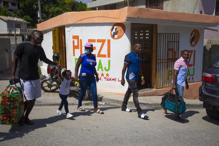 Jhon Celestin, second right, his wife Delta De Leon and their daughter Chloe, deported fron the United States a few days earlier, walk to a bus station in Port-au-Prince, Haiti, Friday, Sept. 24, 2021. De Leon intends to cross the border into the Dominican Republic with her daughter as soon as possible to reunite with her father, sister and brother while her husband flies ahead to Chile. But first, the family will travel to the coastal city of Jacmel in southern Haiti to see more relatives, a risky trip because it entailed crossing gang-controlled territory. (AP Photo/Joseph Odelyn)