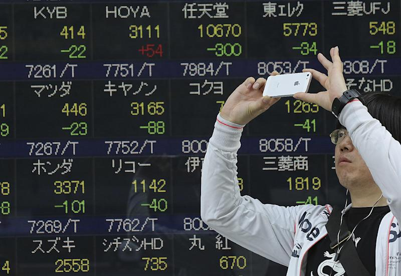A man takes a photo with his smartphone camera in front of an electronic stock board of a securities firm in Tokyo, Wednesday, May 7, 2014. A dismal day on Wall Street spilled over into Asian trading Wednesday as jitters over the valuations of technology companies contributed to a sharp drop in Japan's benchmark. The Nikkei 225 stock index fell 2.3 percent to 14,120.25. Japanese markets were closed the previous two days for public holidays. (AP Photo/Eugene Hoshiko)