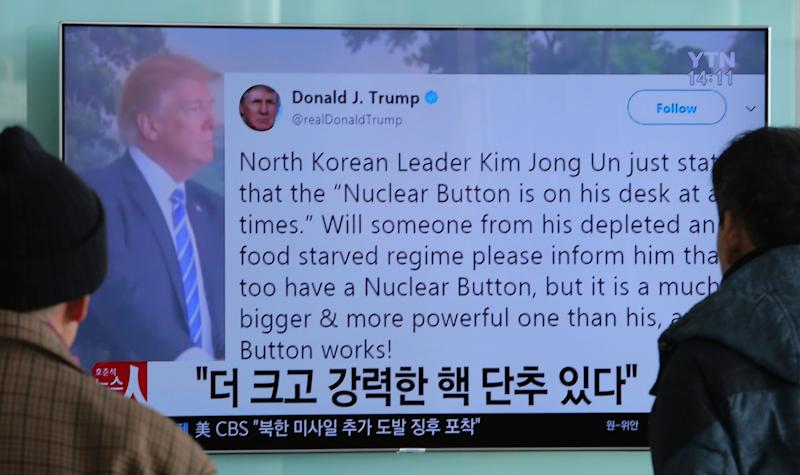 Passersby watch a news program showing a Twitter post from President Donald Trump on North Korea's nuclear weapons program, at Seoul Railway Station in Seoul, South Korea, on Jan. 3, 2018.