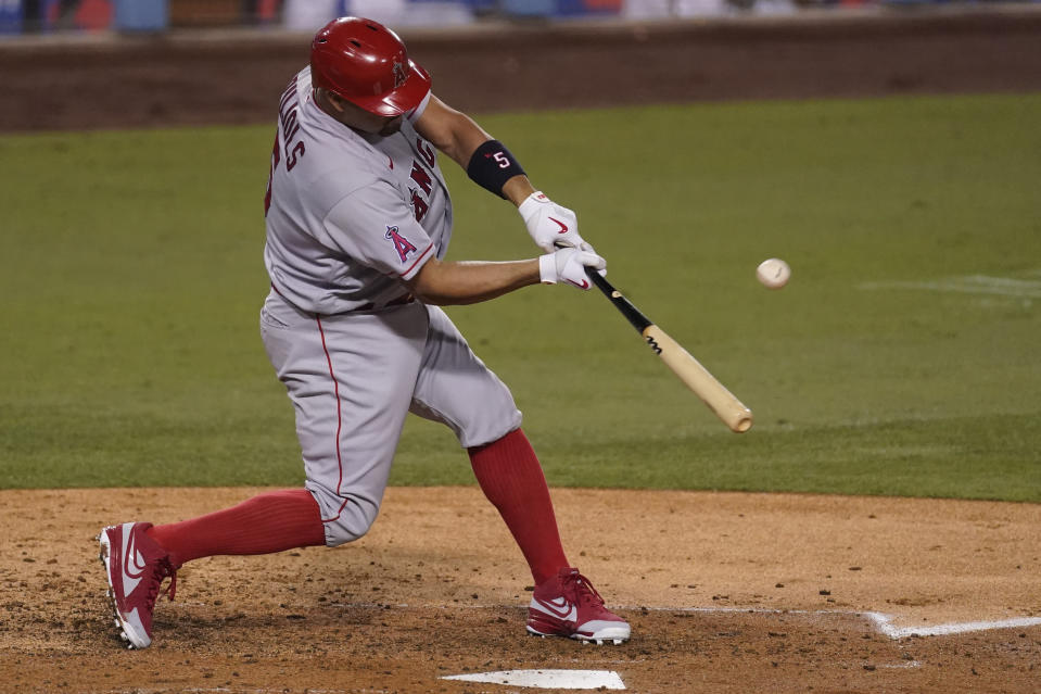 Los Angeles Angels' Albert Pujols hits a sacrifice fly to center field during the third inning of a baseball game against the Los Angeles Dodgers, Saturday, Sept. 26, 2020, in Los Angeles. Angels' Jared Walsh scored on the play. (AP Photo/Ashley Landis)