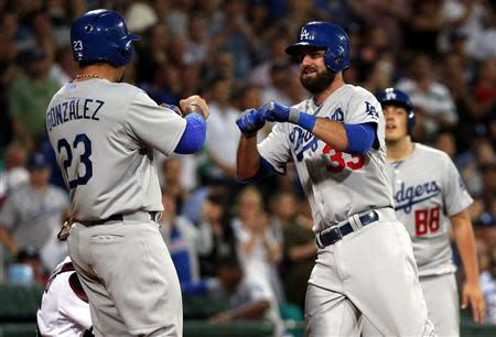 Los Angeles Dodgers batter Van Slyke (C) celebrates with team mates as he crosses home-plate after hitting a home run against the Arizona Diamondbacks during the top of the fourth innings of the opening game of the 2014 Major League Baseball season at the Sydney Cricket Ground March 22, 2014. REUTERS/David Gray