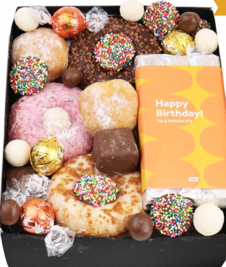 five donuts, a 'Happy Birthday' block of chocolate and other confectionery